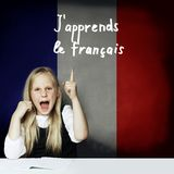 Learn french language concept. Happy child girl student pointing up. On the tittle J`apprends le francais stock images