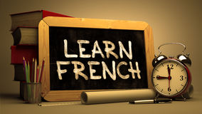 Learn French - Motivational Quote on Chalkboard. Learn French - Motivational Quote Handwritten on Chalkboard. Time Concept. Composition with Chalkboard and Stack Stock Image