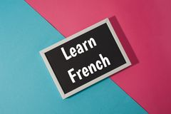 Learn French - text on chalkboard on blue and pink Stock Image