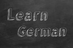 Learn German. Hand drawing `Learn German` on blackboard stock illustration