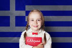 Learn greek language. Smart child girl on Greece flag. Background stock photo