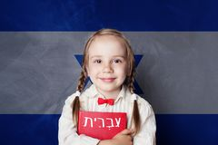 Learn hebrew language. Smart child girl on Israel flag. Background stock images