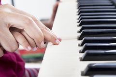 Learn how to play piano. Closeup of hand guiding little piano player playing the piano in the musical class Stock Photos