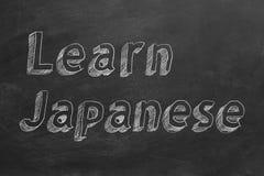 Learn Japanese. Hand drawing `Learn Japanese` on blackboard stock illustration