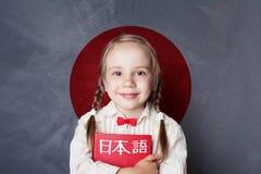 Learn japanese language. Smiling kid pupil on Japan flag. Background stock photo