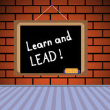 Learn and lead. Blackboard with the text learn and lead written with chalk Royalty Free Stock Photos
