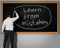Learn from Mistakes Concept. Businessman writing Learn from Mistakes words with chalk on a blackboard in front of him Stock Photos