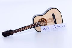 Die Gitarre, German word for Guitar in English. Learn new German word, die Gitarre note near a guitar. White background royalty free stock images