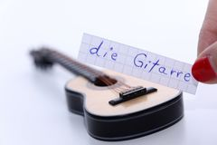 Die Gitarre, German word for Guitar in English. Learn new German word, die Gitarre note near a guitar. White background stock photo