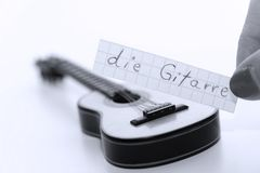 Die Gitarre, German word for Guitar in English. Learn new German word, die Gitarre note near a guitar. White background royalty free stock photography