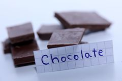 Chocolate, English word on a white note, pieces of chocolate on background. Learn new language, English word for Chocolate written on a note near some chocolate Stock Photography