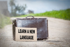 Learn a New Language. Old traveling suitcase on country road.  stock image