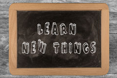 Learn new things -  chalkboard. Learn new things - chalkboard with 3D outlined text - on wood Royalty Free Stock Images