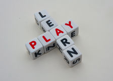 Learn and play. Text ' learn ' and ' play ' inscribed on small white cubes and combined crossword style with common letter ' a ' isolated on bright background Stock Photography