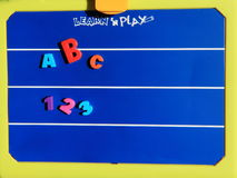 Learn and play board. A blue play board with some letters and numbers ilustrating the concept of learning Royalty Free Stock Images