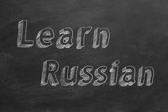 Learn Russian. Hand drawing `Learn Russian` on blackboard stock illustration