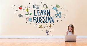 Learn Russian text with little girl using a laptop computer. On floor stock photos