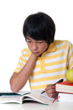 Learn for school. Young student make his homework against white background Stock Photos