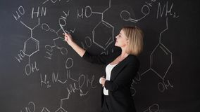Learn science or chemistry formula confident beautiful woman teacher chalk blackboard background.  stock footage