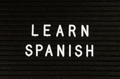 Learn Spanish language, modern looking sign on black background. Learn languages sign on black background royalty free stock photo