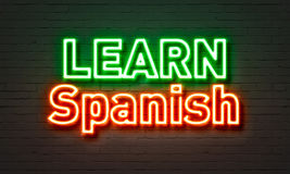 Learn Spanish neon sign on brick wall background. Stock Image