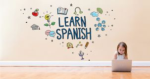 Learn Spanish text with little girl using a laptop computer. On floor stock photos