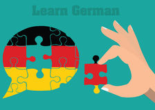 Learn and speak german conceptual illustration. Hand with puzzle comlete dialog bubble Royalty Free Stock Photography