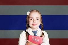 Learn Thai language. Thailand concept with kid little girl student with red book against the Thailand flag background stock image