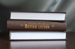 Learn to be a better lover. Book concept. Books on a table and one with  Learn to be a better lover.  cover. Book concept Stock Photo