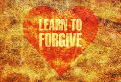 Learn to forgive. Text Learn to Forgive written with golden letters on a red heart Royalty Free Stock Image