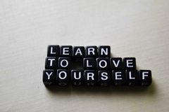 Learn to Love Yourself on wooden blocks. Business and inspiration concept royalty free stock photo