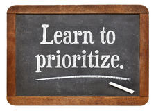 Learn to prioritize. Motivational advice on a vintage slate blackboard Royalty Free Stock Photos