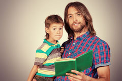 Learn to read. Happy father reading a book to his adorable son Stock Images