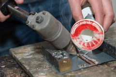 Learn to solder and train - detail. Manual worker learns to solder with soldering iron and solder wire - close-up of metal work stock images