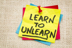 Learn to unlearn advice. Learn to unlearn - advice or motivation words on a sticky note against burlap canvas Stock Photo
