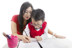 Learn to write. Portrait of elementary school student learn to write with his mother Royalty Free Stock Photo
