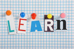 Learn. The word Learn in cut out magazine letters pinned to a background of blue graph paper Royalty Free Stock Photos