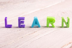 Learn. The word learn written on white wooden surface Stock Image