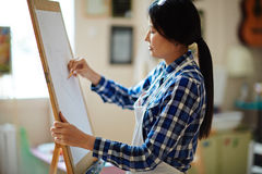 Learner of art studio. Young girl drawing on paper with pencil in studio of arts Royalty Free Stock Images