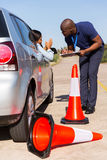 Learner driver apologising. Female african learner driver apologizing to instructor after running over traffic cone Stock Photos