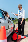 Learner driver apologising. Female learner driver apologising to angry instructor after running over traffic cone royalty free stock photo