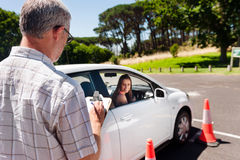 Learning to drive. Learner driver girl with instructor taking lessons Royalty Free Stock Photography