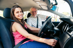 Learning to drive. Learner driver girl with intstructor taking lessons Royalty Free Stock Photo