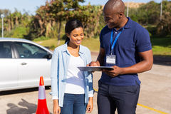 Learner driver instructor. African learner driver with instructor before talking driving test royalty free stock images