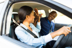 Learner driver instructor. Cheerful young african learner driver and driving instructor high five Royalty Free Stock Image