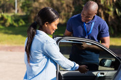 Learner driver instructor. Happy female african learner driver with instructor doing pre driving inspection stock images