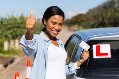 Learner driver's license. Attractive african learner driver holding her driver's license Royalty Free Stock Photography