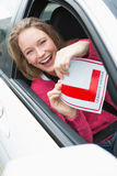 Learner driver smiling and holding l plate Royalty Free Stock Photos