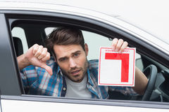 Learner driver smiling and holding l plate Royalty Free Stock Image
