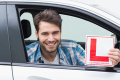 Learner driver smiling and holding l plate Royalty Free Stock Photo